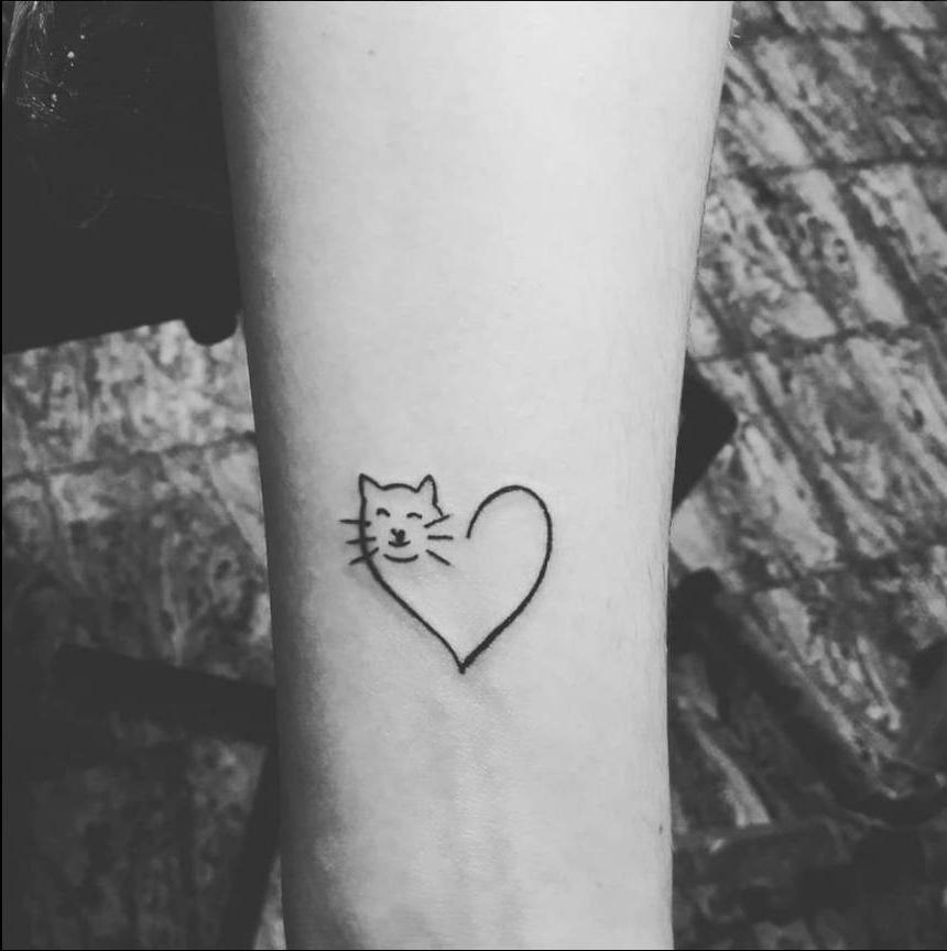 Pequeno tatuaje de gato corazon en la muneca