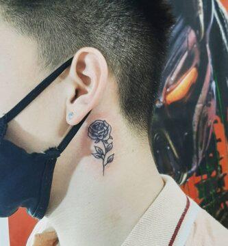 Pequeño tatuaje de risa en el cuello cerca de la oreja