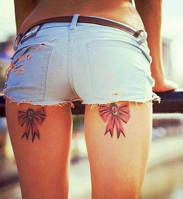 Tatuaje en la pierna de mujer liguero con dos lazos rojos en la parte posterior del muslo