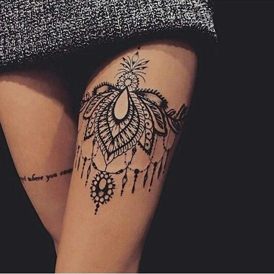 Tatuaje en la pierna de mujer liguero flor y plumas en la inscripcion del muslo en la otra pierna