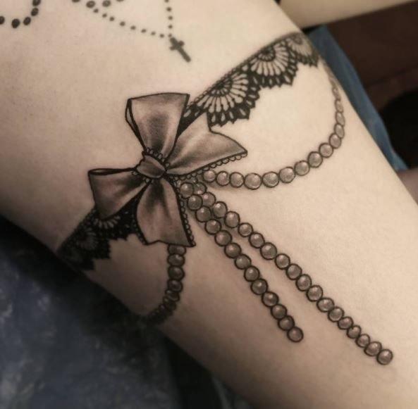 Tatuaje en la pierna de mujer liguero lazo de liguero con perlas