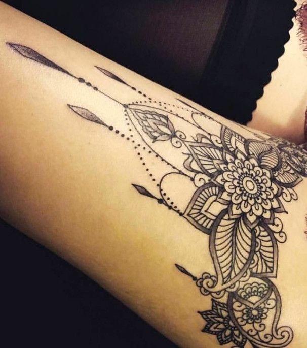Tatuaje en la pierna de mujer liguero motivo con flores y hojas y colgantes en negro