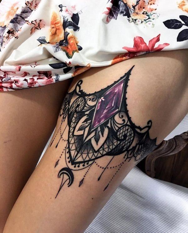 Tatuaje pierna de mujer liguero piedra violeta en forma de rombo con llamador de ageles