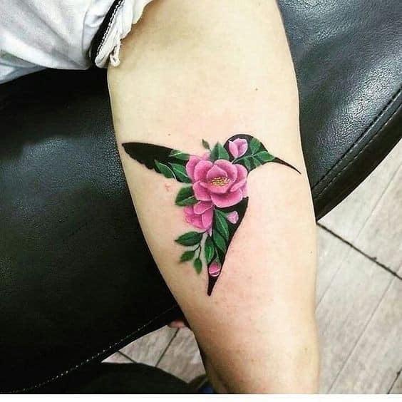 Tatuajes de Colibries Mujer con fondo de flores rosas y ramas verdes