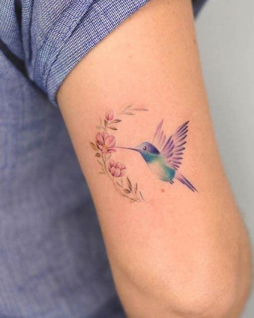 Tatuajes de Colibries Mujer picando flor rosa en brazo