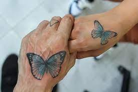 Tatuajes de Mariposas Azules dos manos de madre e hija