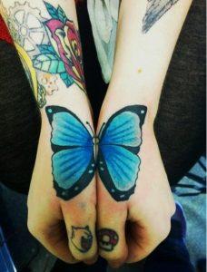 Tatuajes de Mariposas Azules en dos dedos pulgar una ala en cada dedo