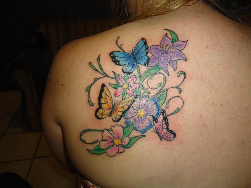 Tatuajes de Mariposas Azules en un entorno de flores y otras mariposas