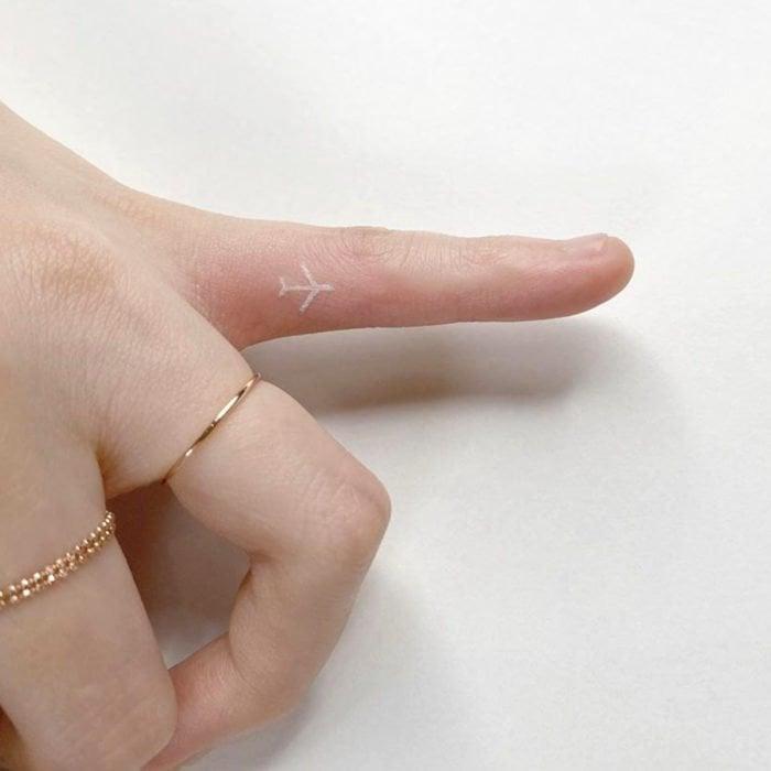 Tatuajes super pequenos para mujeres avion en tinta blanca en dedo