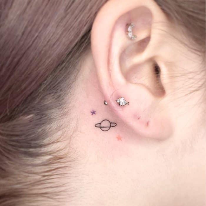 Tatuajes super pequenos para mujeres estrellas y saturno detras de la oreja