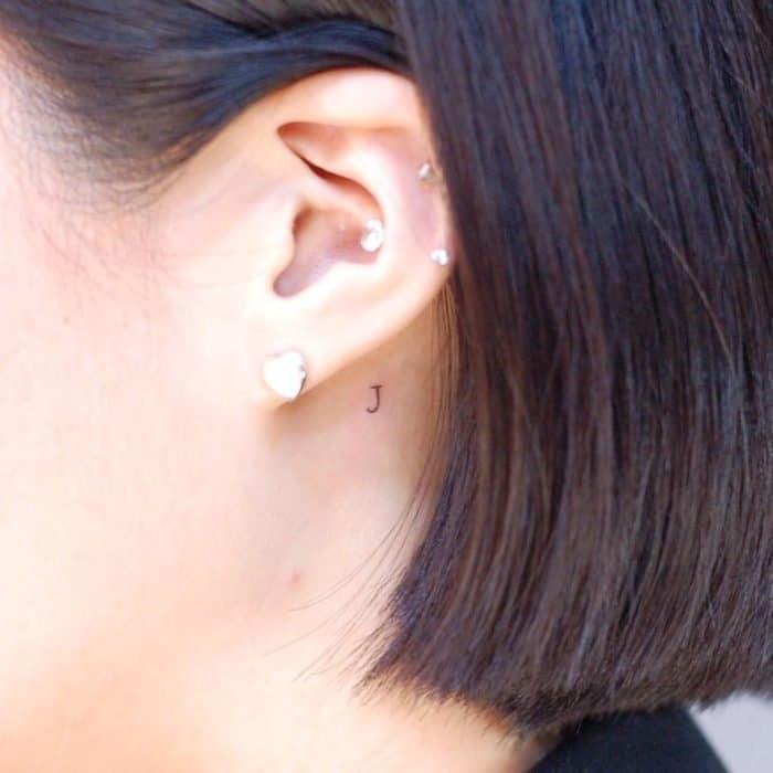 Tatuajes super pequenos para mujeres letra J detras de la oreja