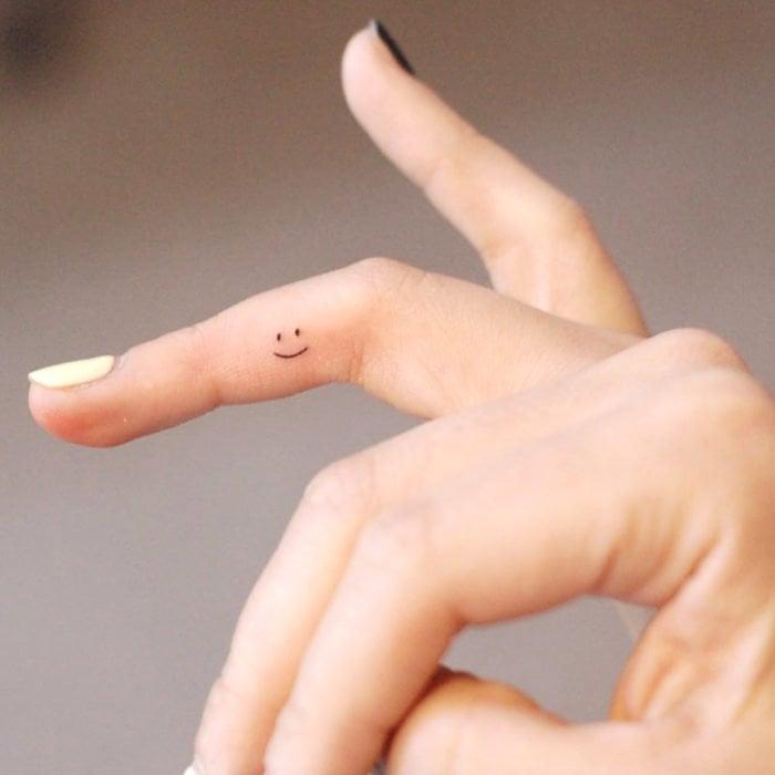 Tatuajes super pequenos para mujeres sonrisa smile en dedo