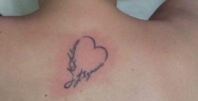 Pequeño tatuaje de corazon en espalda cerca del cuello con delicadas letras