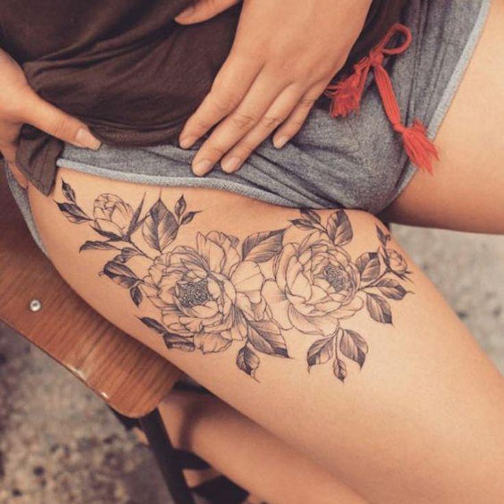 tatuaje de mujer en zona de pierna flores y ramas