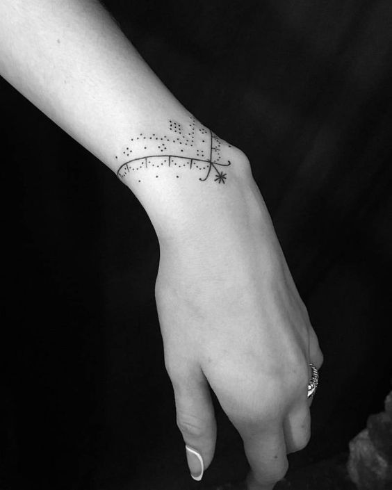 tatuaje en mujeres zona muneca estilo brazalete delicadisimo motivo con puntos y lineas